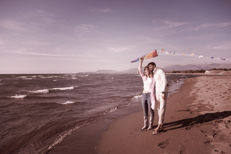 Young Couple having fun and Playing With A Kite On The Beach at autumn day filter