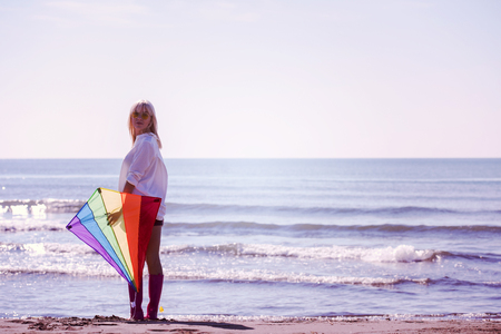 Beautiful Young Woman having fun with a kite at Beach on autumn day filter