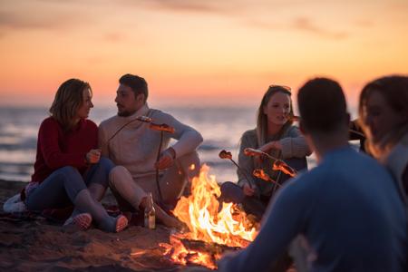 Groupe de jeunes amis assis près du feu à la plage d'automne, griller des saucisses et boire de la bière, parler et s'amuser