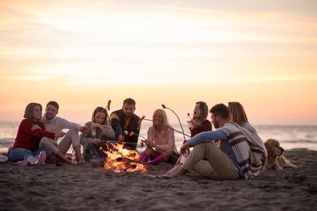 Groupe de jeunes amis assis près du feu à la plage d'automne, griller des saucisses et boire de la bière, parler et s'amuser Banque d'images