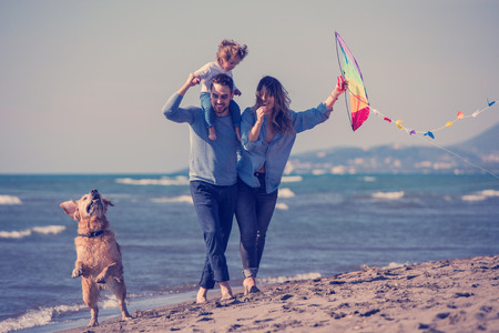 happy young family with kids having fun with a dog and  kite at beach during autumn day