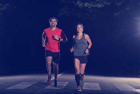 市内の公園でジョギングをしている健康な人々のグループ、夜間トレーニングでランナーチーム