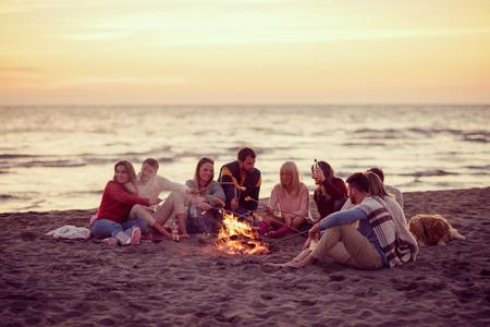 Groep jonge vrienden zitten bij het vuur op herfst strand, worstjes grillen en bier drinken, praten en plezier filteren