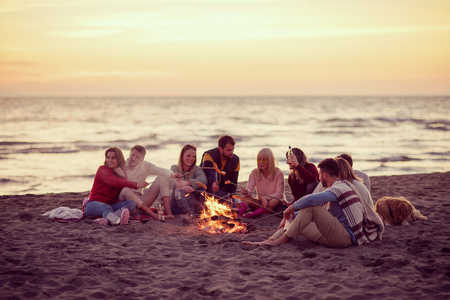 Group of young friends sitting by the fire at autumn beach, grilling sausages and drinking beer, talking and having fun filter
