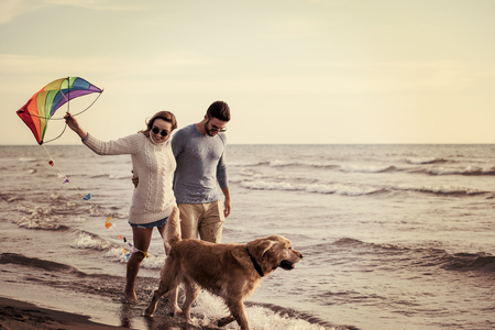 Young Couple having fun playing with a dog and Kite on the beach at autumn day filter