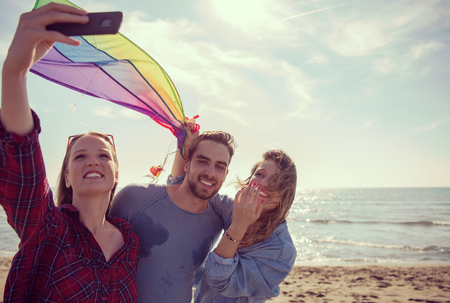 group of young friends making selfie while playing with kite on a beach during sunny autumn day filter