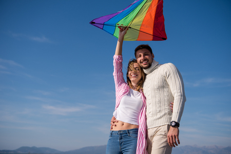 Young Couple having fun and Playing With A Kite On The Beach at autumn day