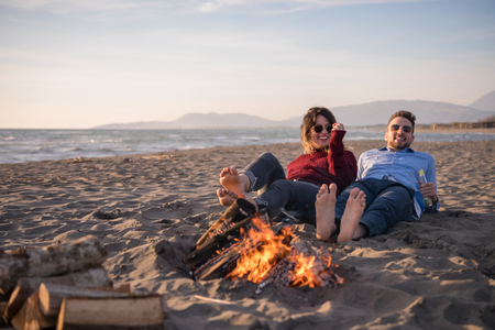 Young Couple Relaxing By The Fire, Drinking A Beer Or A Drink From The Bottle on the beach at autumn day 스톡 콘텐츠