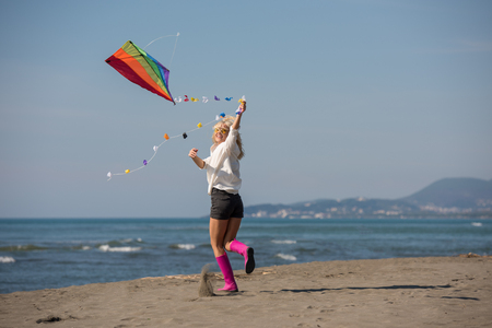 Beautiful Young Woman having fun with a kite at Beach on autumn day Stock Photo
