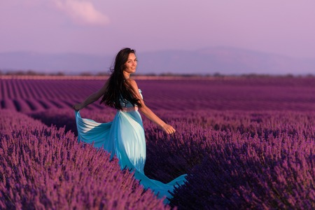 lavander flower field woman in cyand dress having fun and relax on wind in  purple flower field Stock Photo