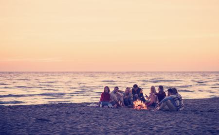 Group of young friends sitting by the fire at autumn beach, grilling sausages and drinking beer, talking and having fun Banque d'images