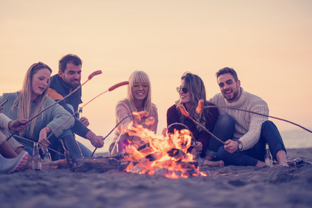 Group of young friends sitting by the fire at autumn beach, grilling sausages and drinking beer, talking and having fun Stockfoto