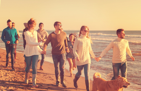 group of young friends spending day together running on the beach during autumn day Stock Photo