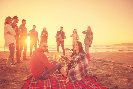 Young Couple enjoying with friends Around Campfire on The Beach At sunset drinking beer Stok Fotoğraf - 107530995