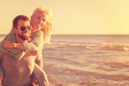 Men Giving Piggy Back Rides to his girlfriend At Sunset By The Sea, autumn time