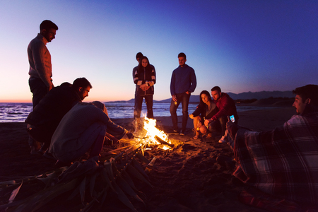 Happy Carefree Young Friends Having Fun And Drinking Beer By Bonefire On The Beach As The Sun Begins To Set Stock Photo