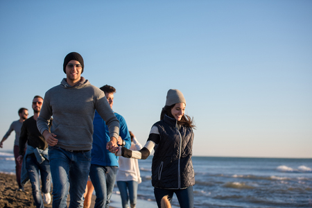 group of young friends spending day together running on the beach during autumn day Reklamní fotografie