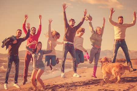 Group of excited young friends jumping together at sunny autumn beach Stock Photo