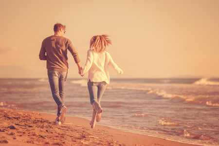 Young couple having fun walking and hugging on beach during autumn sunny day Stock Photo - 107562953