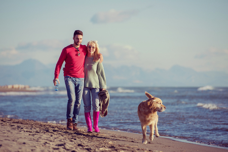 Couple Running On The Beach Holding Their Hands with dog On autmun day Stock Photo