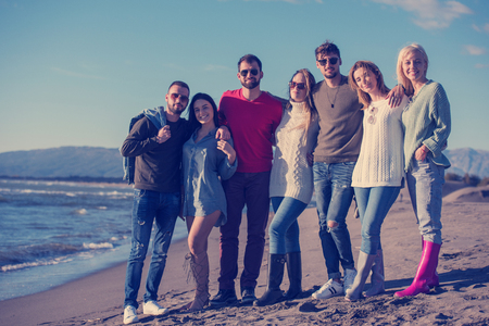 portrait of group Friends Spending The Day On A Beach during autumn day Stock Photo