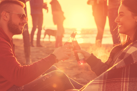 Young Couple enjoying with friends Around Campfire on The Beach At sunset drinking beer Stok Fotoğraf - 108116352