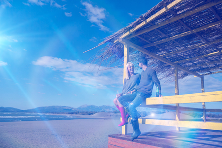 Couple Drinking Beer Together in empty beach bar during autumn time