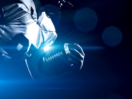 American football player holding ball while running on field at night Stock Photo