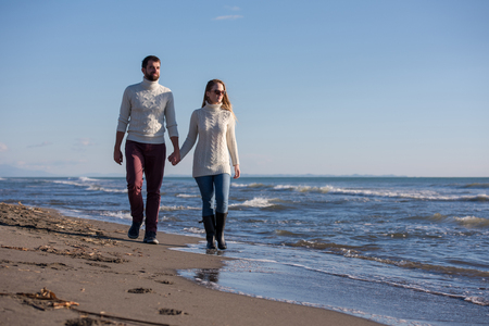 Young couple having fun walking and hugging on beach during autumn sunny day