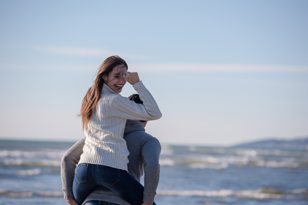 Men Giving Piggy Back Rides his girlfriend At Sunset By The Sea, autumn time Stock fotó