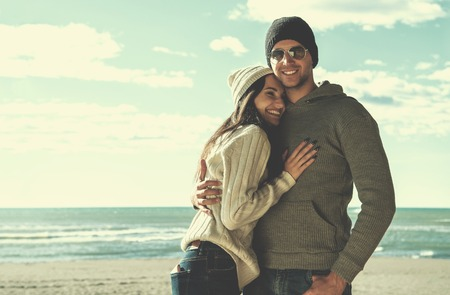 Happy couple enyojing time together on beach during autumn day Reklamní fotografie