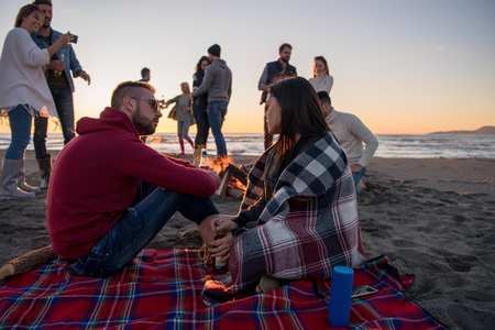 Young Couple enjoying with friends Around Campfire on The Beach At sunset drinking beer