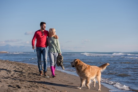 Couple Running On The Beach Holding Their Hands with dog On autmun day Фото со стока