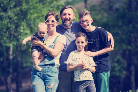 portrait of happy young big hipster family while  having picninc and fun time in nature