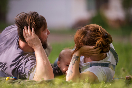 hipster family relaxing in park and playing with baby on beautiful sunny spring day