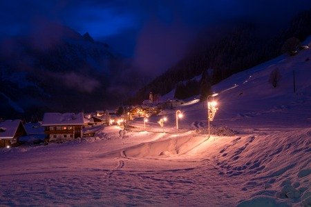mountain village in alps  at night in winte  with fresh snow Stockfoto