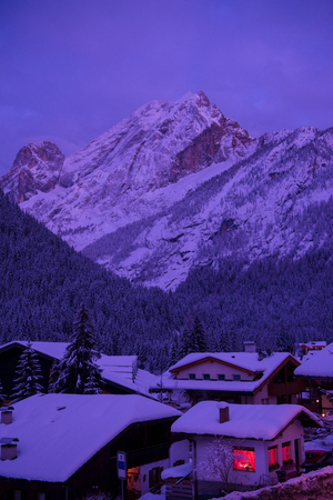 mountain village in alps  at night in winter  with fresh snow