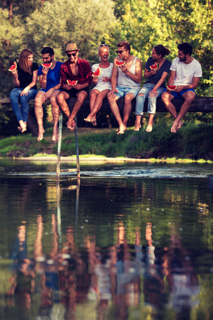 group of young friends enjoying watermelon while sitting on the wooden bridge over the river in beautiful nature Stockfoto - 109457947