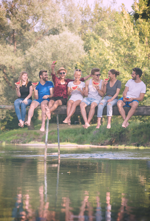 group of young friends enjoying watermelon while sitting on the wooden bridge over the river in beautiful nature Stock Photo - 109698553