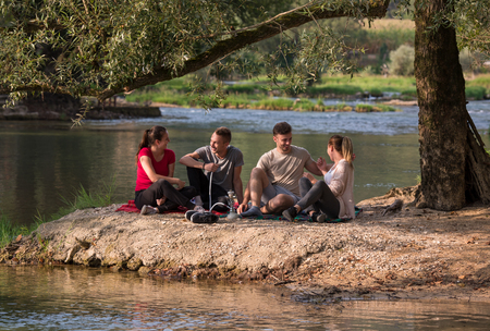 group of young friends enjoying beautiful sunny day while smoking hookah on the river bank