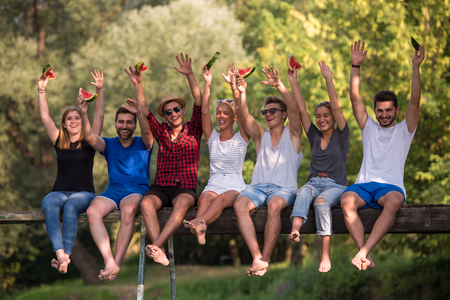 group of young friends enjoying watermelon while sitting on the wooden bridge over the river in beautiful nature Stockfoto - 109698611