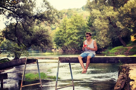 young man enjoying watermelon while sitting on the wooden bridge over the river in beautiful nature