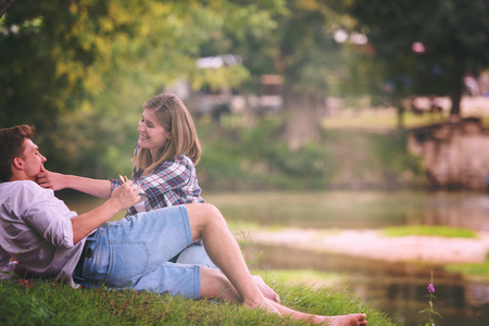 Couple in love enjoying picnic time drink and food in beautiful nature on the river bank Stock Photo