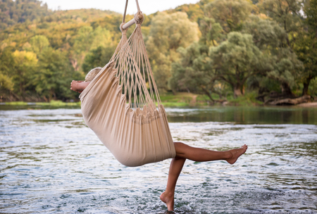 Young blonde woman resting on hammock while enjoying nature on the river bank