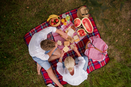 Couple in love enjoying picnic time drink and food in beautiful nature on the river bank top view Stock Photo