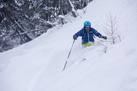 freeride skier with rucksack skiing downhill on fresh powder snow