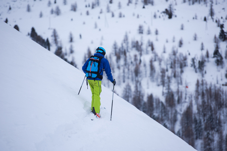 freeride skier with rucksack skiing downhill on fresh powder snow Stock Photo