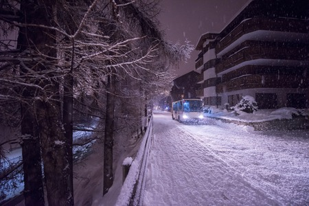 Electric taxi bus on snowy streets in the car-free Alpine mountain village at cold winter night Foto de archivo - 110231951