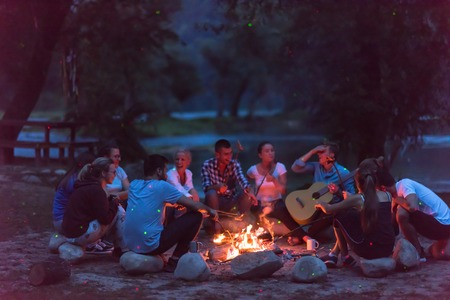 a group of happy young friends relaxing and enjoying  summer evening around campfire on the river bank Banque d'images