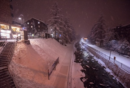 a view on snowy streets of the Alpine mountain village in the cold winter night